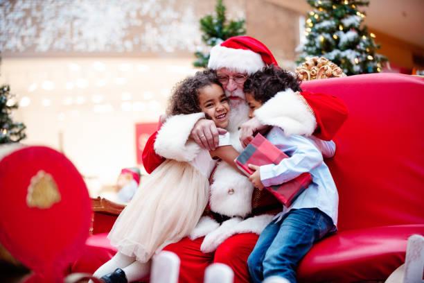 shopping-weihnachten mit der familie und santa claus beim einkaufszentrum - santa stock-fotos und bilder