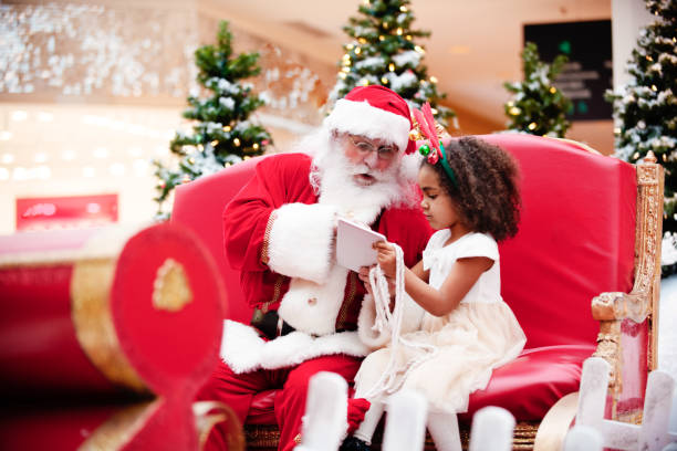 shopping christmas with family and santa claus at shopping mall - manonallard stock photos and pictures
