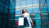 istock Shopping concept. Afro woman shopaholic in white beautiful dress holding many paper shopping bags in front of business building with blue windows 1170150576