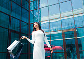 istock Shopping concept. Beauty afro woman in white beautiful dress holding many paper shopping bags on background of business building with blue windows 1170150444