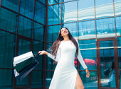 istock Shopping concept. Beauty afro woman in white beautiful dress holding many paper shopping bags on background of business building with blue windows 1170150496
