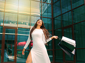 istock Shopping concept. Beauty afro woman in white beautiful dress holding many paper shopping bags on background of business building with blue windows 1211167987