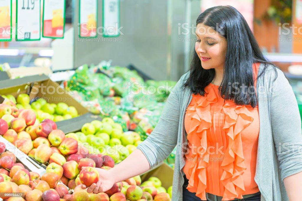 Conceito de compras. Apple de tomada de mulher na loja de supermercado. - foto de acervo