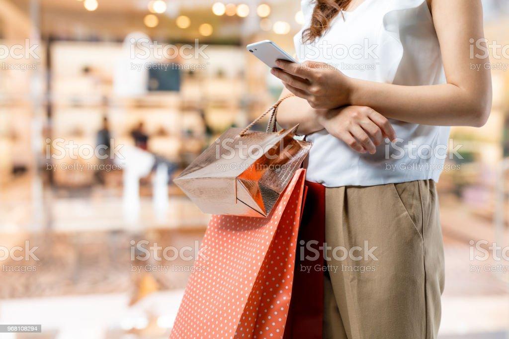 winkelen op concept. vrouw met behulp van slimme telefoon met boodschappentas. - Royalty-free Alleen volwassenen Stockfoto