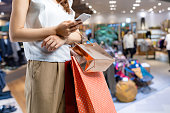 istock shopping concept. woman using smart phone with shopping bag. 968108306