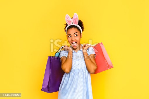 Young woman wearing cute dress and bunny ears headband standing isolated on yellow background holding shopping bags looking aside mouth opened smiling playful