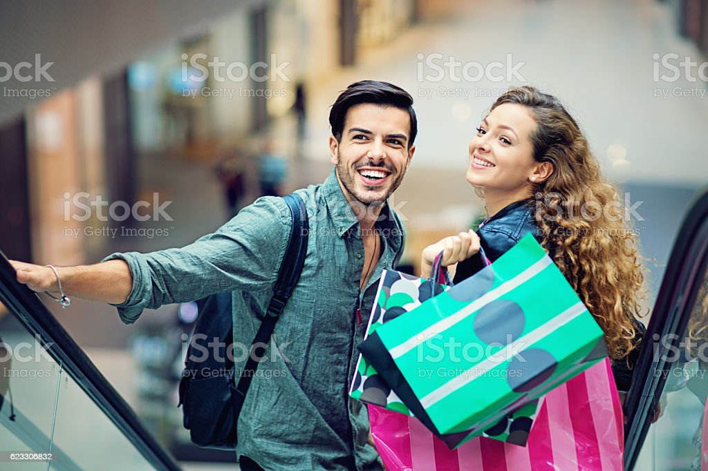 Shopping couple are laughing on the escalator in Mall - foto de acervo