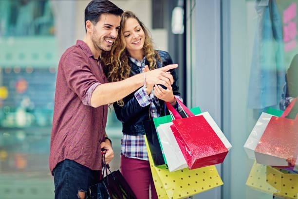 shopping couple is  looking in the store window in the mall - taschen von liebeskind stock-fotos und bilder