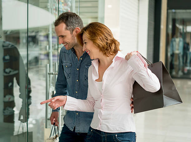 Shopping couple looking at a window stock photo
