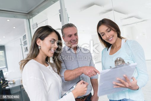 Shopping couple talking to saleswoman at a store and looking very happy
