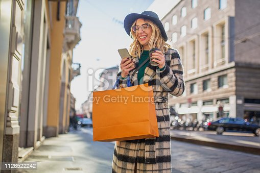 Carefree woman shopping downtown, holding coffee and using mobile phone