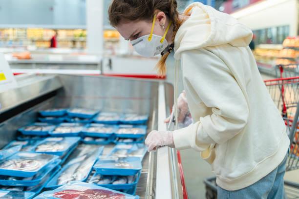 Einkaufen während einer Pandemie. Eine junge Frau mit Schutzmaske und Handschuhen, die in einem Supermarkt Fisch kauft. – Foto