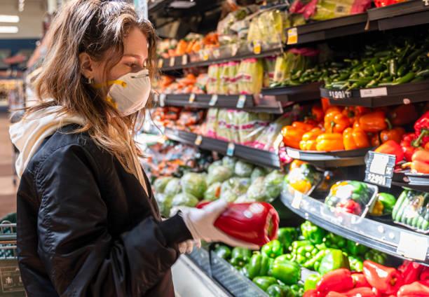 Einkaufen während einer Pandemie. Eine junge Frau mit Schutzmaske und Handschuhen beim Gemüsekauf in einem Geschäft. – Foto