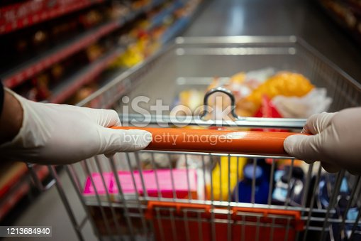 Woman using gloves during shopping in supermarket.