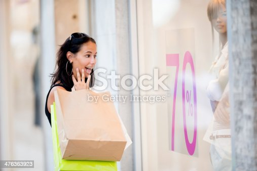Young woman walking down the street holding a lot of shopping bags and sudenly spot a -70% off sale.