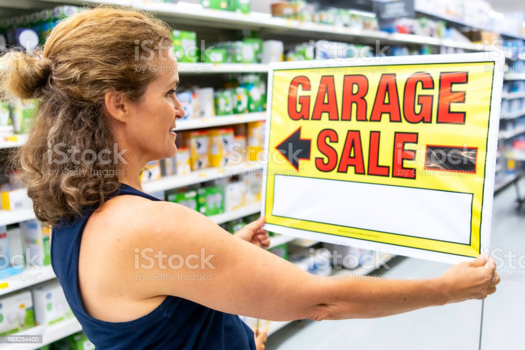 Mature caucasian Woman looking at a \'garage sale\' sign in a...