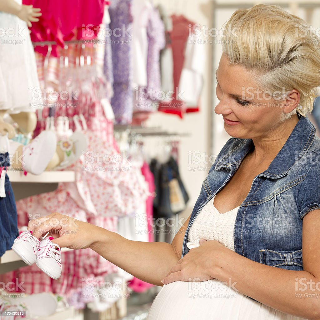 Shopping for baby clothes, holding shoes stock photo