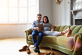 Shot of a pregnant woman and her husband sitting on thier sofa using a digital tablet