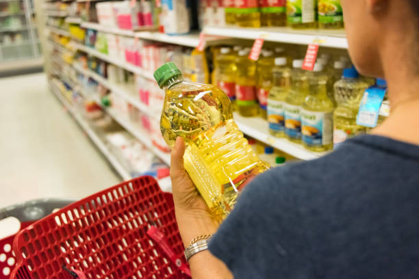 Shopping for cooking oil Caucasian housewife shopping for vegetable oil in a supermarket alley discount store stock pictures, royalty-free photos & images