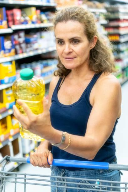 shopping for cooking oil - palm oil bottles imagens e fotografias de stock