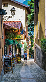 Bellagio, Italy-May 29, 2011-A young  man pauses along a narrow walkway to examine the featured menu of a small cafe in Bellagio, Italy