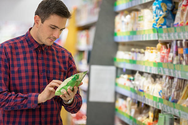 Shopping for snacks Man choosing snacks in supermarket snack aisle stock pictures, royalty-free photos & images