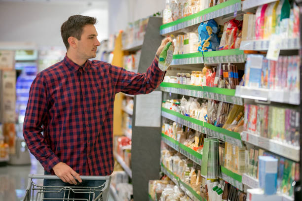 Shopping for snacks Man choosing healthy eating in supermarket snack aisle stock pictures, royalty-free photos & images