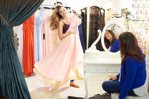 shopping for that dress A young woman holds a dress to her body in a dress boutique and twirls for her mother who is helping her to choose. The dress is elaborate and could be a ball gown , prom dress, or bridesmaid gown. evening wear stock pictures, royalty-free photos & images