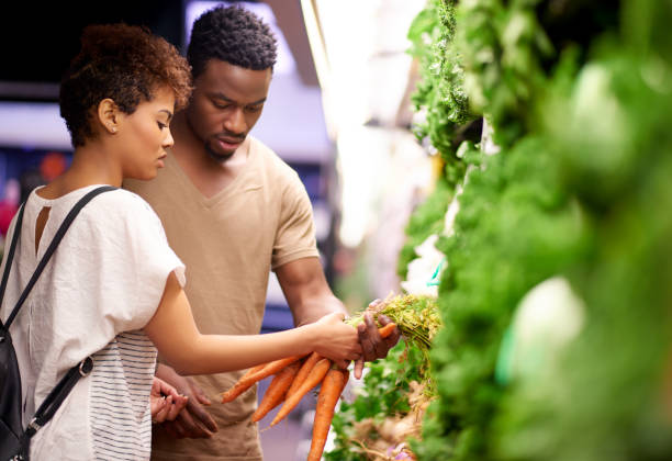 Shopping for the freshest produce at the best price Shot of a young couple shopping in a grocery store market retail space stock pictures, royalty-free photos & images