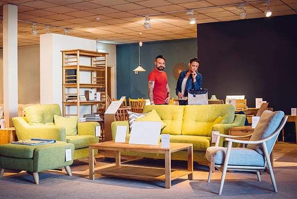 Shopping for the New Home A middle aged couple are shopping in a furniture store for items for their new home. they are both browsing the living room items and look thoughtful. showroom stock pictures, royalty-free photos & images