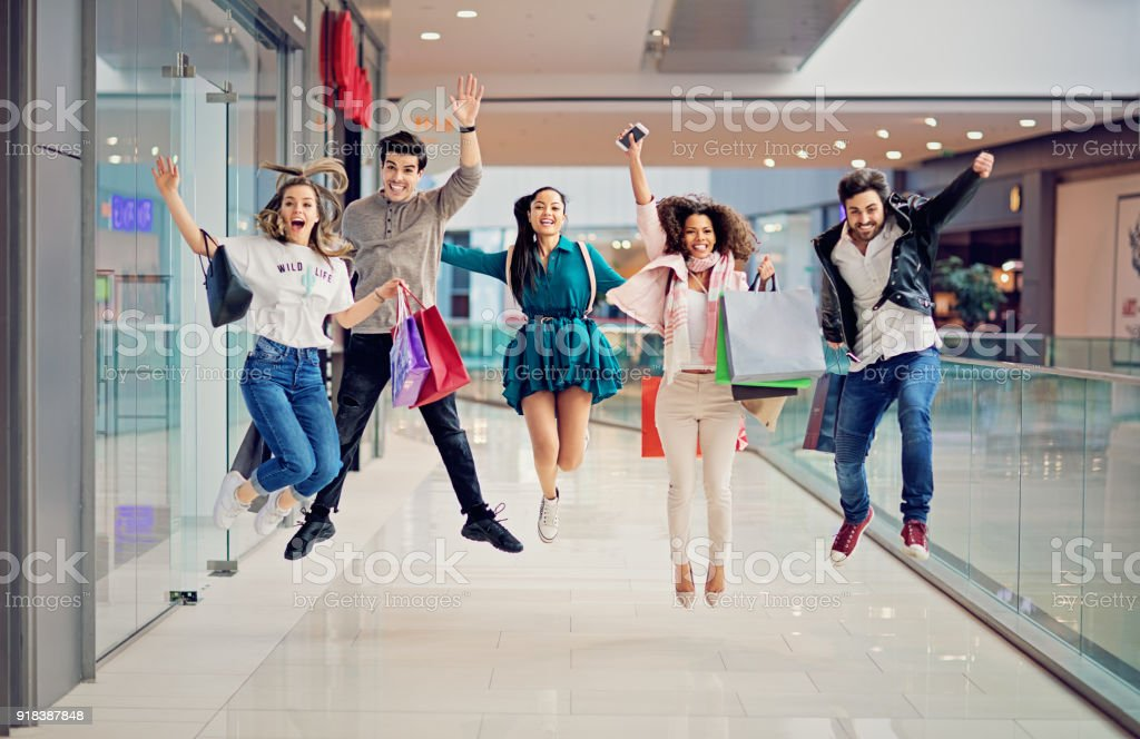 Shopping friends are jumping in the Mall stock photo