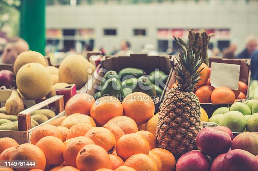 istock Shopping fruit on the marketplace in Belgrade. Orange, pineapple, apples, avocado, melon in baskets ready for sale. Blurred customers on background. 1149781444