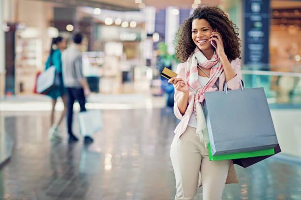 shopping-mädchen hält ihre kreditkarte und sprechen in der mall - handytasche stock-fotos und bilder