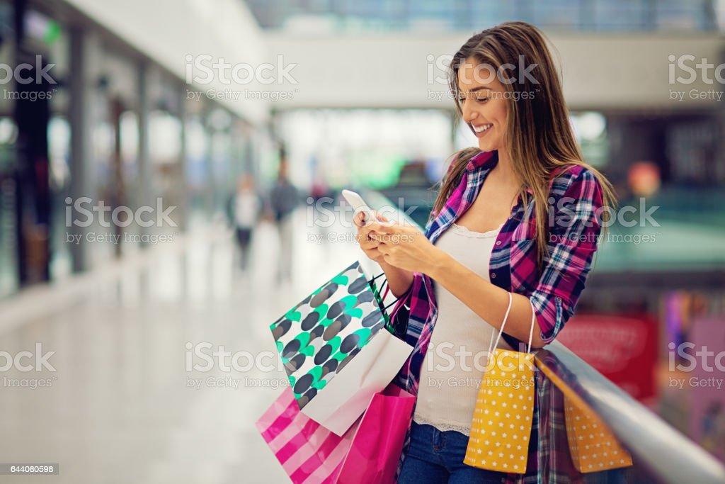 Menina compra está digitando no shopping - foto de acervo