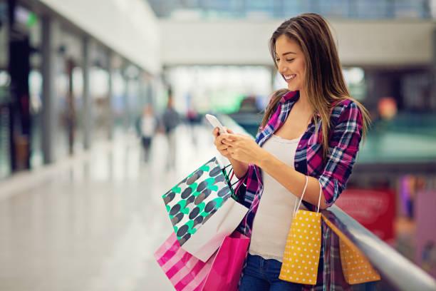 shopping-mädchen ist sms in der mall - handytasche stock-fotos und bilder
