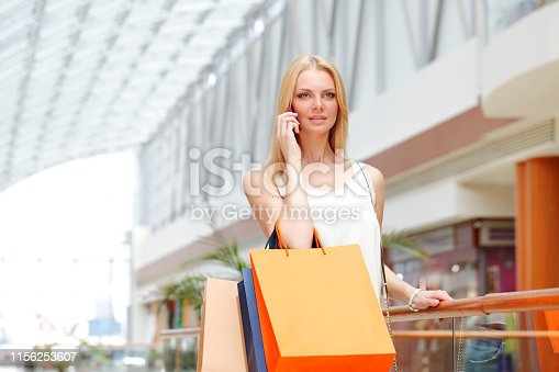 Shopping girl with bags talking on the phone in mall