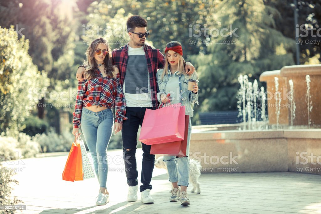 Shopping girls and man are walking after shopping around the town royalty-free stock photo