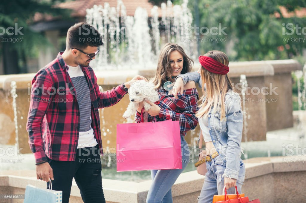 Shopping girls and man are walking after shopping around the town zbiór zdjęć royalty-free