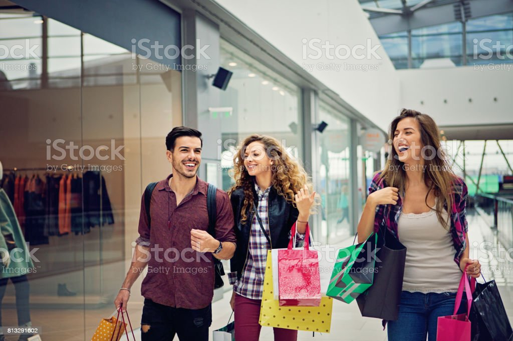 Shopping girls and man are walking in the Mall stock photo
