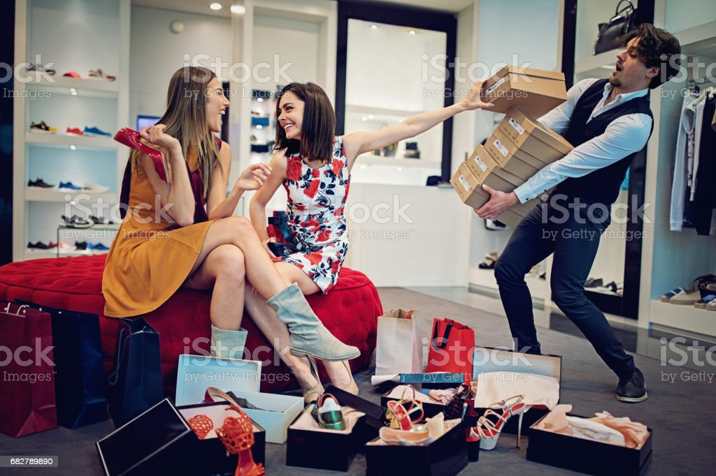 Shopping girls are choosing shoes and asking from salesman for more stock photo