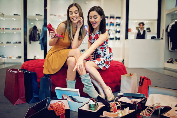 Shopping girls are choosing shoes in a boutique and make fun stock photo