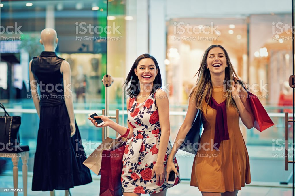 Shopping girls are entering in a clothes store stock photo