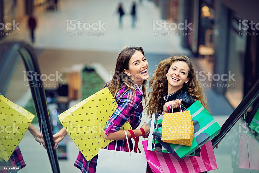 Shopping girls are laughing on the escalator in Mall stock photo