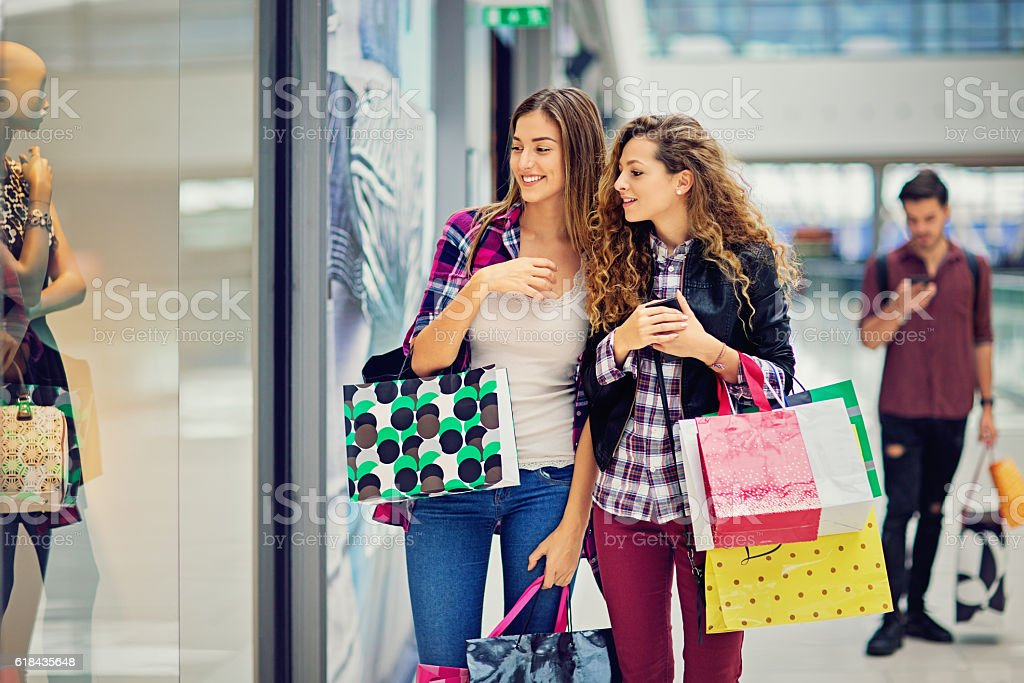 Shopping girls are looking dresses in Mall stock photo