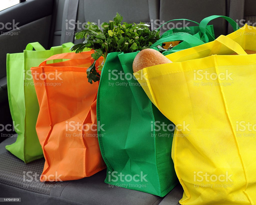 Shopping Green Four filled and colorful eco-friendly shopping bags in the back seat of a car. Back Seat Stock Photo