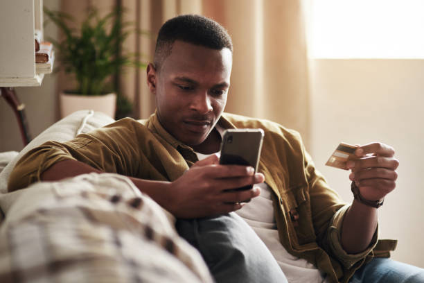 Shopping has never been more convenient Cropped shot of a handsome young man using a smartphone and a credit card to shop online while sitting on his couch at home phone charging stock pictures, royalty-free photos & images