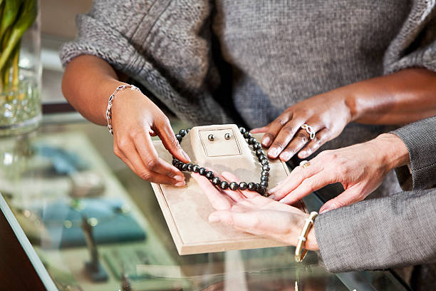 Shopping in jewelry store Hands of saleswoman helping customer look at merchandise in jewelry store. jeweller stock pictures, royalty-free photos & images