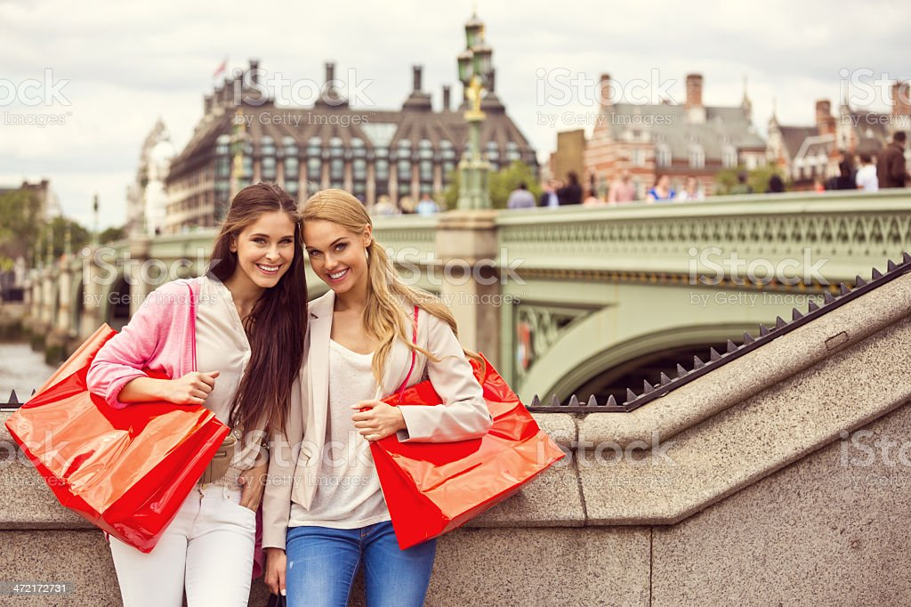 Shopping in London Outdoor portrait of two happy young women carrying shopping bags smiling at camera with Westminster Bridge in the background. 20-24 Years Stock Photo