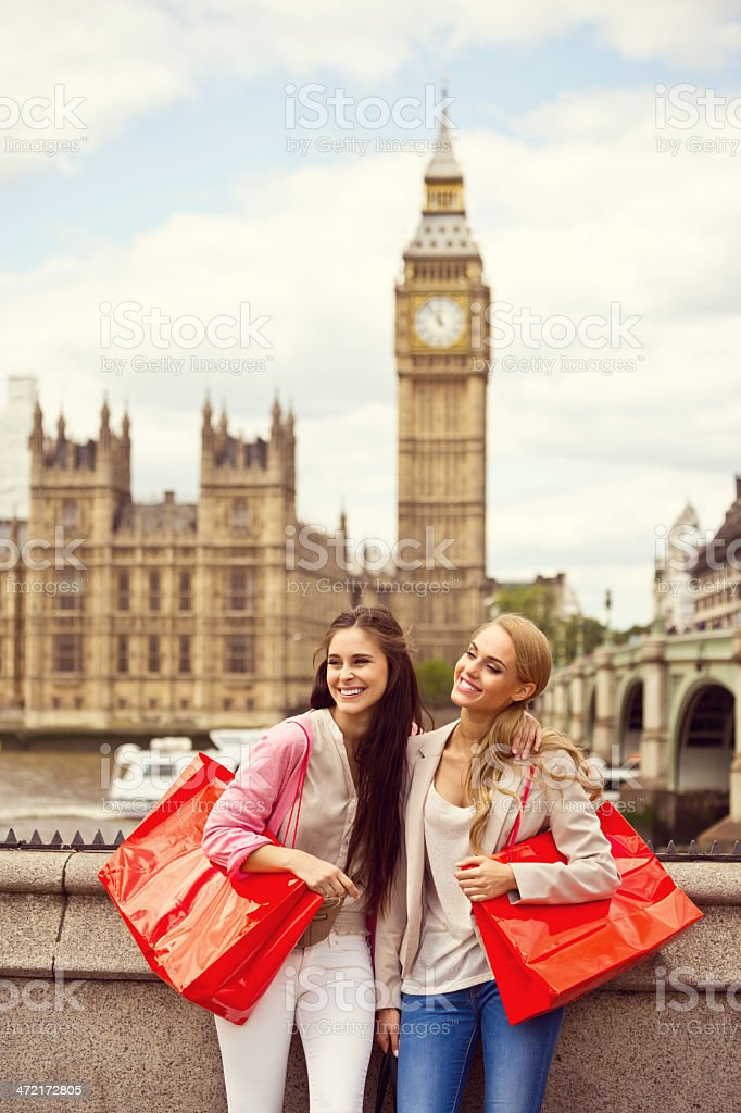Shopping in London Outdoor portrait of two happy young women with Houses of Parliament and Big Ben in the background. 20-24 Years Stock Photo