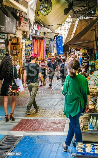 Athens, Greece-May 3, 2018-Tourists and locals shop along the narrow alleys and pedestrian streets for trinkets and  souvenirs in the Plaka section of Athens, Greece.